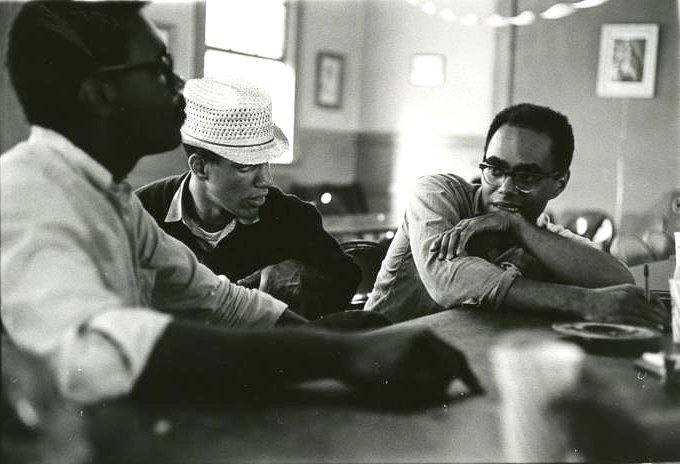 Three men sitting at a lunch counter, in the center is Ivanhoe Donaldson, to the right of him is presumably Julian Bond.